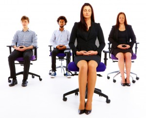 group of young businesspeople meditating in office chairs